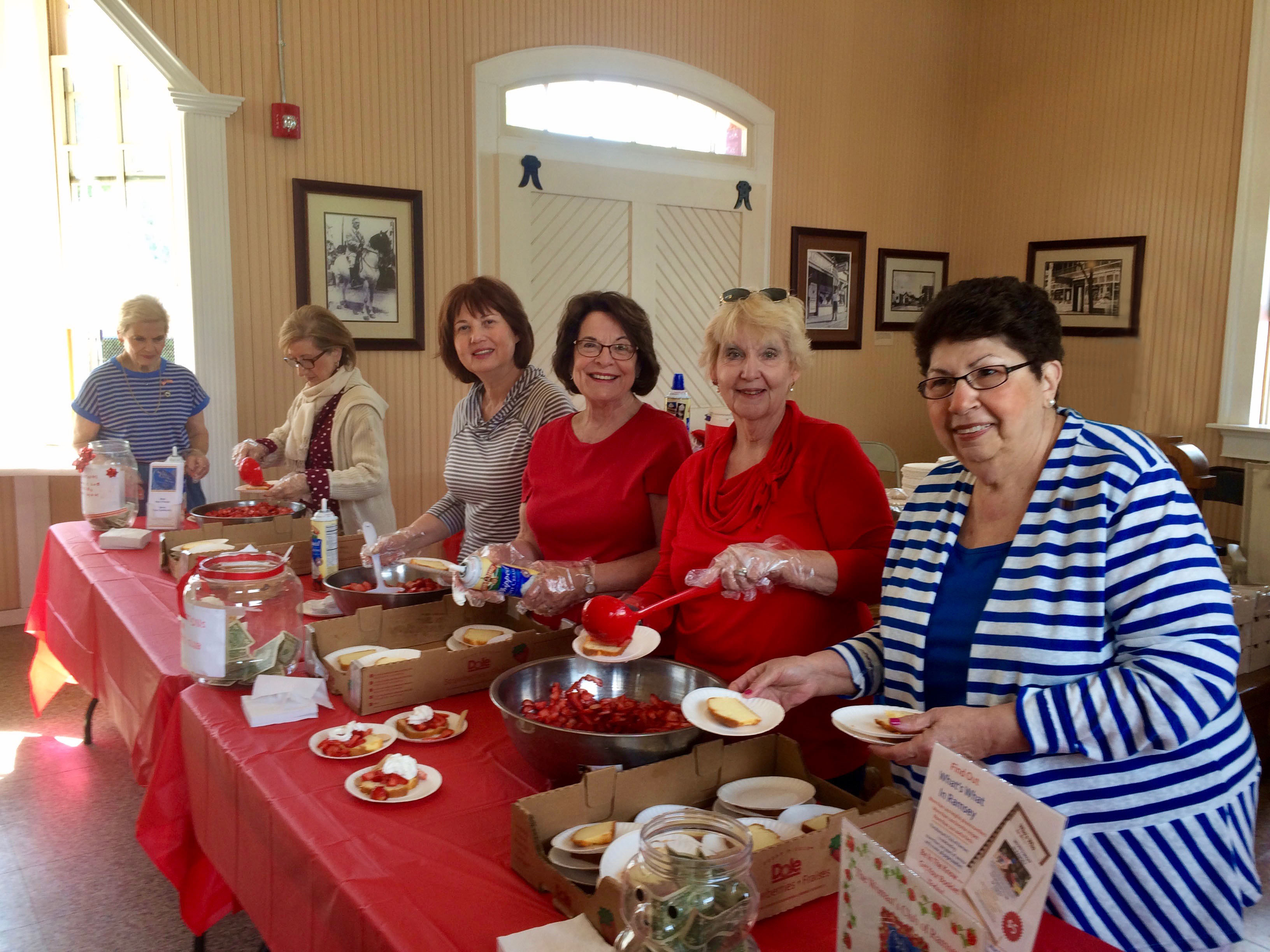 Marjorie Detweiler, Toni Small, Verda Kesedar, Dorothy Verdone, Pat Bernius, and Tina Pellicciari offer free strawberry shortcake at the Ramsey train depot.